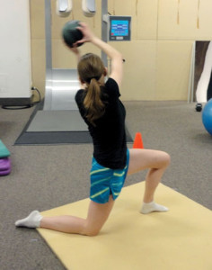 Figure 2.  Trunk rotation with medicine ball resistance performed in half-kneeling position. This exercise helps integrate core and hip strength, postural control, and coordination to improve dynamic knee stability in standing.