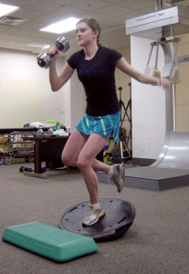 Figure 3.  Single-leg dumbbell clean and press on Bozu ball to improve dynamic knee stability, trunk and lower extremity postural alignment, and balance and coordination during single-leg stance.