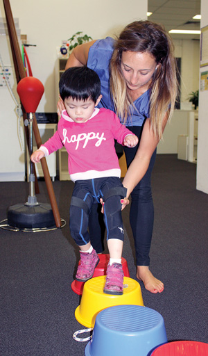 This child, aged nearly 4 years, was diagnosed with mi- crocephaly, autism spectrum disorder, and hypotonia. She uses sensomotoric orthoses in Piedro boots and receives regular physiotherapy for gait, gross motor skills, motor planning, and strength. She also undergoes occupational therapy. (Photo courtesy of Therapies for Kids.)
