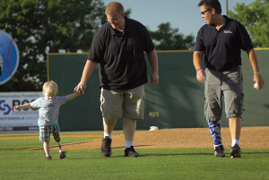 "John ""Mo"" Kenney, CPO, (far right) takes a walk with his youngest patient and the patient's father. (Photo courtesy of Kenney Orthopedics.)"