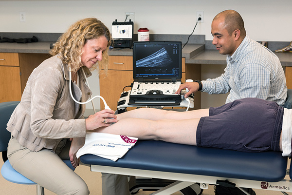 Karin Silbernagel, PT, PhD, ATC, and Daniel Cortes, PhD, use ultrasound to examine a patient's Achilles tendon. (Photo courtesy of Karin Silbernagel, PT, PhD, ATC.)