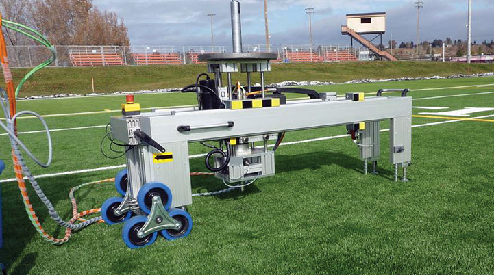 Figure 2. Photograph of the footwear traction tester performing a traction test on the field of play with the athlete's actual shoes used for competition.