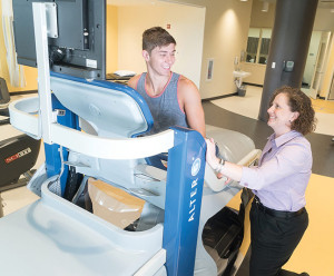 Figure 3. The clinic director of the outpatient clinic at Rio Sport&Health in Gaithersburg, MD, assists a patient on the antigravity treadmill, which helps reduce recovery time from a sports-related injury or orthopedic condition.