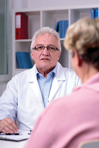 Doctor is talking with a woman in his office