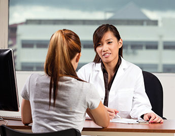 Asian doctor talking with female patient